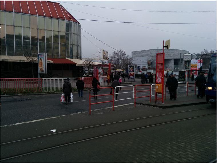 Chodci využívajúci najmenej bariérový neoficiálny priechod zo zastávky električiek do tržnice.