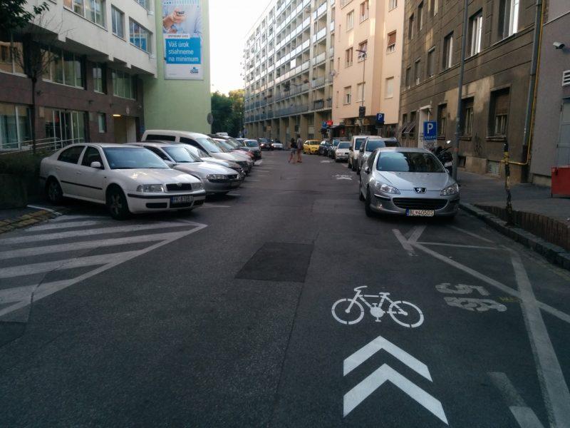 Cyklisti musia dávať pozor na spolujazdcov, ktorý vystupujú smerom do vozovky, autá by mali parkovať vo vyznačených boxoch, nie ako strieborný Peugeot na fotografii.