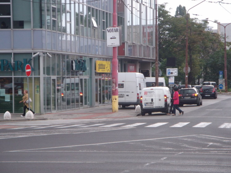 Biskupské klobúky na zabránenie parkovania na chodníku a žltá čiara. Napriek tomu sa parkuje aj na žltej čiare (treba však priznať, že zásobovanie tu nemá kde legálne zastať). A parkuje sa aj na chodníku, kvôli biskupským klobúkom však autá jazdia cez priechody pre chodcov. V odraze vidno dodávku, ktorá cúva cez priechod pre chodcov pri vjazde do garáže. Na legálnosť sa ani nemá zmysel pýtať, čo však policajti na bezpečnosť takýchto manévrov?