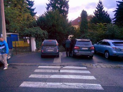 """Vodiči """"mamataxi"""" používajú priechod pre chodcov na zaparkovanie na chodníku, ohrozujúc tým deti idúce peši do školy keď odtiaľ cúvajú."""