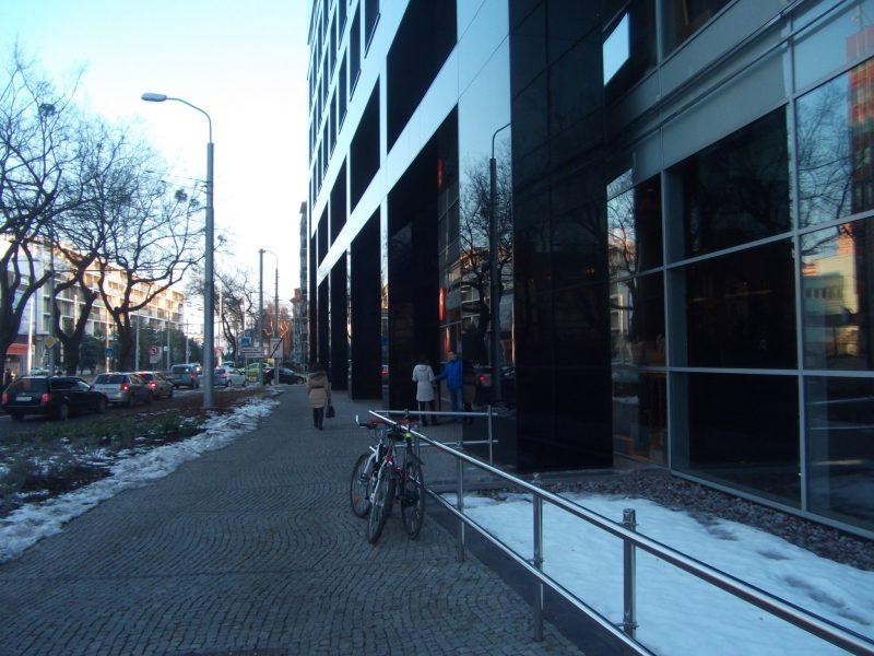 Pri vchode v pozadí sa nenachádza žiadny stojan, zákazníci tak musia pri zamykaní bicyklov hľadať náhradné riešenia.