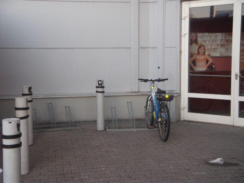 Shopping Palace - bicykle zaparkovaný v stojane, ktorý neumožňuje bezpečné uzamknutie rámu bicykla.