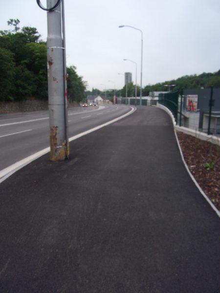 Dostatočne široké  pokračovanie smerom k ZOO. Bohužiaľ však nedošlo k prekládke sĺpov verejného osvetlenia (ideálne vpravo, k plotu), ktoré zbytočne zužujú priestor pre chodcov a cyklistov a vytvárajú potenciálnu nebezpečnú prekážku.