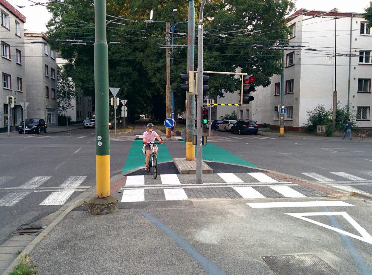 Cyklotrasa R26: Cyklistka prechádza križovatkou počas fázy voľno pre cyklistov. Všimnite si extrémne nízko tyč držiaca semafor, ktorá môže spôsobiť zranenie cyklistu. Na chybu sme mesto upozornili.
