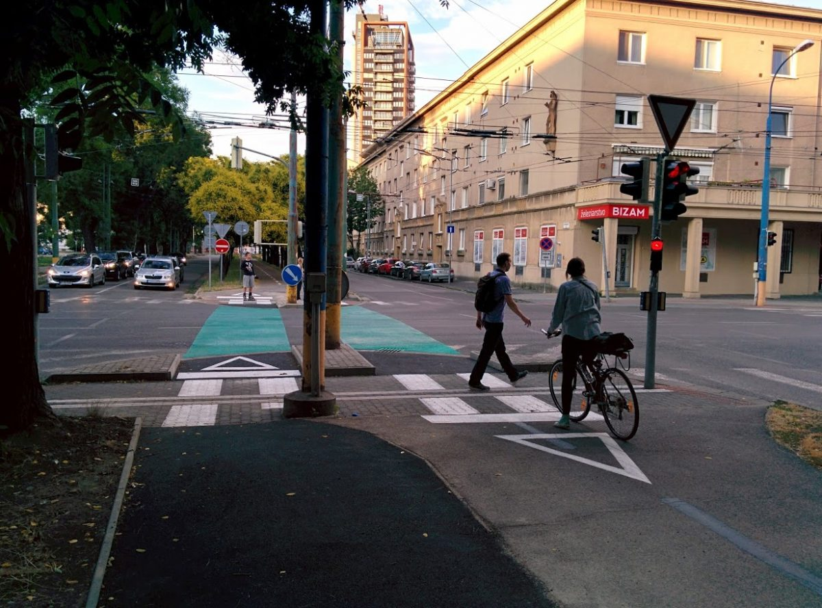 Cyklotrasa R26: Cyklistka čaká na STOP čiare na signál voľno, medzitým chodec prechádza križovatkou.