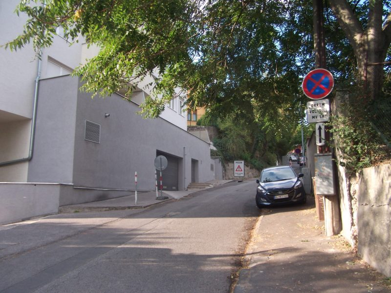 Úplne zbytočná značka zákaz zastavenia. Na takejto úzkej ulici nie je možné zastaviť priamo zo zákona. Nezostalo by buď 1,5 metra voľného na chodníku, alebo 3 metre pre oba smery jazdy na vozovke. V každom prípade, ak má aj auto v pozadí výnimku pre MV SR, ide o státie, nie zastavenie. Ak chcel autor značenia vyhradiť chodník na parkovanie, mal použiť značku povoľujúcu parkovanie na chodníku, nie zákaz zastavenia. No zablokovať jediný chodník vyznačením parkovania by nebolo správne riešenie.