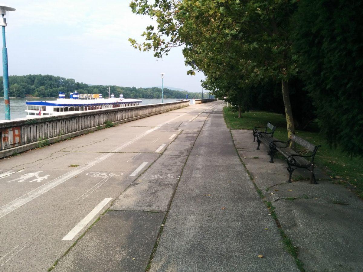 Úsek Most SNP - River Park v súčasnosti. Nechápeme kto a prečo povolil takého hlúpe vyznačenie cyklotrasy stredom nábrežnej pomenády.